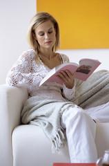 Frau liest ein Buch auf Couch
