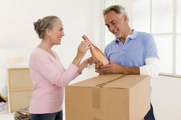 Älteres Ehepaar mit Champagner-Flasche, lächelnd