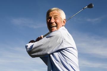 Älterer Mann beim Golfspielen
