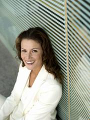 Geschäftsfrau sitzt auf Boden, lächelnd, erhöhte Ansicht, Portrait
