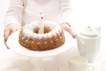 Frau hält Geburtstagskuchen mit einer Kerze