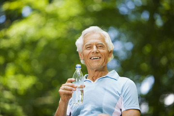 Älterer Mann, trinkt Wasser aus Flasche, Portrait