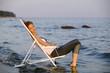 Junge Frau ruht im Liegestuhl am Strand, Seitenansicht