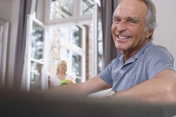 Älterer Mann sitzt am Tisch, lächelnd, Porträt