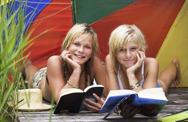 Teenager, Mädchen liegen unter Sonnenschirm am Bootssteg, Buch lesend, Portrait
