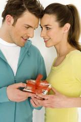 Junges Paar mit Geschenk, Nahaufnahme, lächelnd
