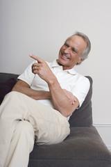 Senior Mann auf dem Sofa, lächelnd, Porträt