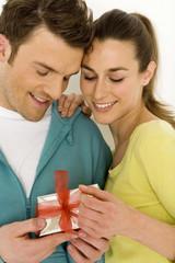 Junges Paar schaut auf Geschenk, lächelnd, Nahaufnahme