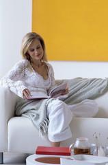Junge Frau liest ein Buch auf dem Sofa