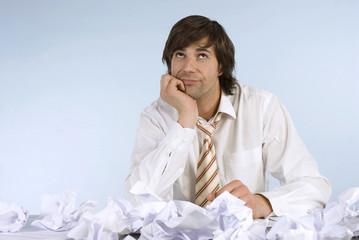 Mann sitzt am Schreibtisch mit zerknüllten Papieren, Blick nach oben