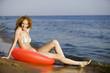 Junge Frau am Strand mit schwimmenden Reifen