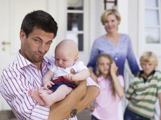 Familie mit Baby vor Eigenheim
