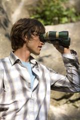 Junger Mann schaut durch ein Fernglas