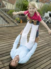 Vater balanciert Tochter auf Füßen