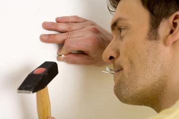Mann schlägt Nagel in die Wand