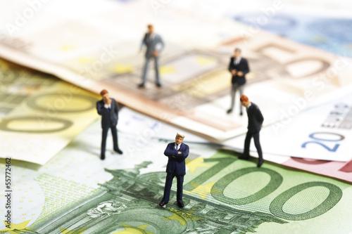Figuren stehen auf Euro-Banknoten
