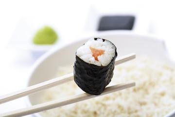 Maki Sushi mit Stäbchen über Schüssel Reis, Nahaufnahme