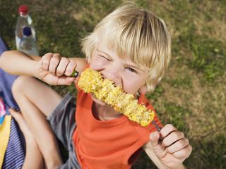 Junge isst Maiskolben, Portrait
