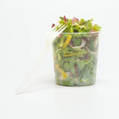 Gabel mitgemischtem Salat in Plastikschale