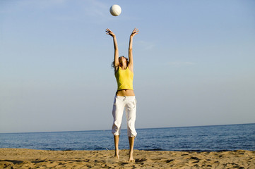 Junge Frau am Strand, Ball spielen