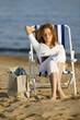 Junge Frau sitzt im Liegestuhl am Strand, Buch lesend