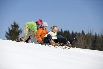 Österreich, Mädchen mit Schlitten im Schnee spielen