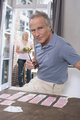 Älterer Mann spielt Solitär, ältere Frau in der Tür stehend, Porträt