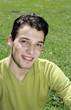 Junger Mann sitzt auf dem Rasen, Portrait, Nahaufnahme