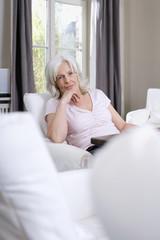 Seniorin sitzt im Wohnzimmer, Portrait