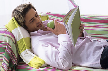 Junger Mann liegt auf dem Sofa, liest Buch, Seitenansicht