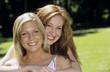 Zwei junge Frauen umarmen sich im Garten, Nahaufnahme, Portrait