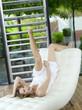 Junge Frau liegt kopfüber auf Relaxsessel, lächelnd