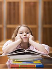 Mädchen sitzt am Schreibtisch, stützt sich auf Stapel Bücher