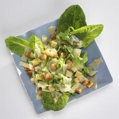 Salat auf Teller mit gebratenem Brot und Soße