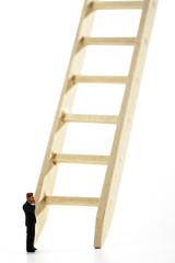 Businessmann-Figur steht vor Leiter