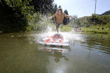 Junger Mann springt auf Luftmatratze