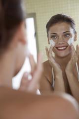 Junge Frau benutzt Gesichtscreme