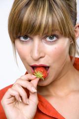 Junge Frau isst Erdbeere