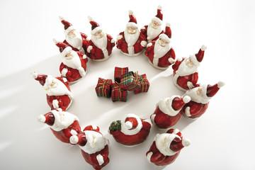 Weihnachtsmann-Figuren stehen im Kreis