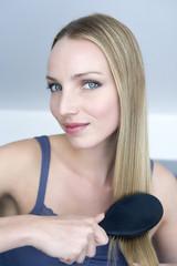 Junge Frau, die ihr Haar bürstet, Portrait
