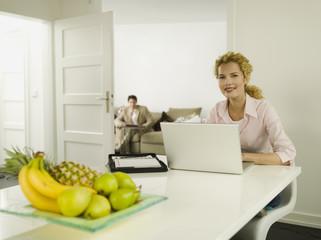 Junge Frau mit Laptop, Mann im Hintergrund
