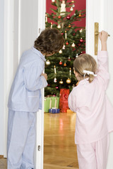 Mädchen und Junge schauen durch die Tür ins Weihnachtszimmer