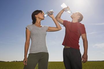 Junges Paar trinkt Wasser aus Flasche