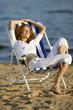 Junge Frau sitzt im Liegestuhl am Strand, die Augen geschlossen
