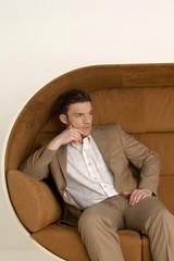 Geschäftsmann sitzt auf Sofa und schaute weg