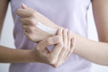 Frau cremt ihre Hände ein