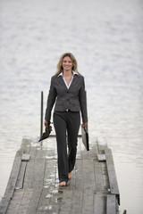 Geschäftsfrau zu Fuß auf Anlegestelle, hält Schuhe in der Hand