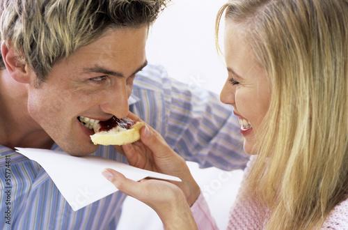 Frau füttert Mann mit Kuchen mit Marmelade, Nahaufnahme