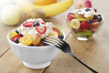 Sweet tasty fruit salad in the bowl with whipped cream