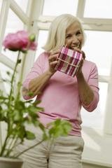 Ältere Frau mit Geschenk-Box, lächelnd